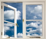 a window looks out onto a blue sky full of clouds