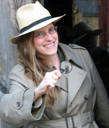 photo photo of Kathy MacMillan in an overcoat and fedora, holding a magnifying glass